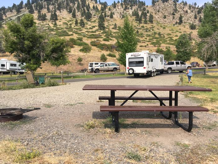 Interior view of campground from Site 6 at Holter Lake Campground. Hillside in the background across from Beartooth Road. Graveled campsite with paved access.Site 6 BLM Holter Lake Campground.