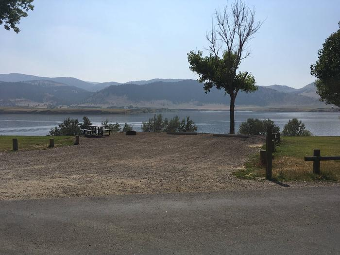 Site 12 BLM Holter Lake Campground. Paved access to campsite. Graveled campsite with picnic table and fire pit. Trees dispersed throughout campground. Unblocked view of Holter Lake.Site 12 BLM Holter Lake Campground.