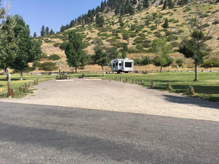 Site 16 BLM Holter Lake Campground. Interior campsite with lakeside campsite across from the paved access. Graveled campsite with picnic table and fire pit. Trees dispersed throughout campground.Site 16 BLM Holter Lake Campground
