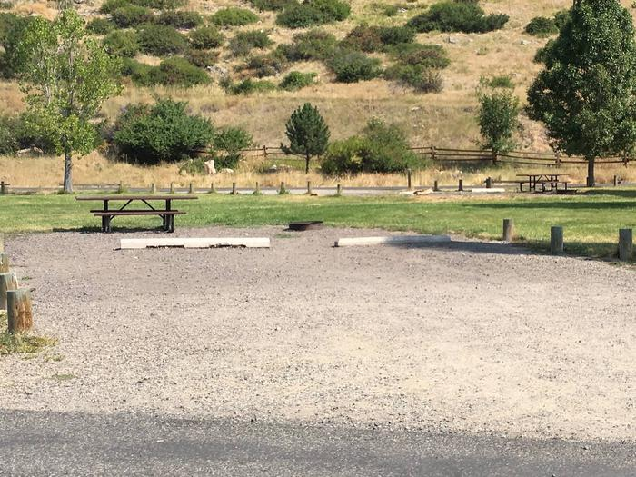 Site 17 BLM Holter Lake Campground. Paved access to campsite. Graveled campsite with picnic table and fire pit. Trees dispersed throughout campground.Site 17 BLM Holter Lake Campground