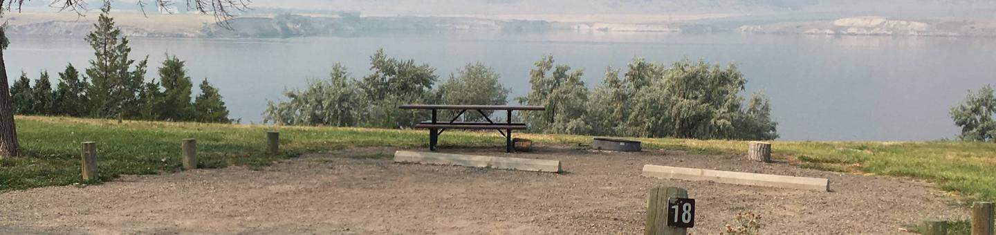 Site 18 BLM Holter Lake Campground. Lakeside campsite with paved access to campsite. Graveled campsite with picnic table and fire pit. Trees dispersed throughout campground.Site 18 BLM Holter Lake Campground