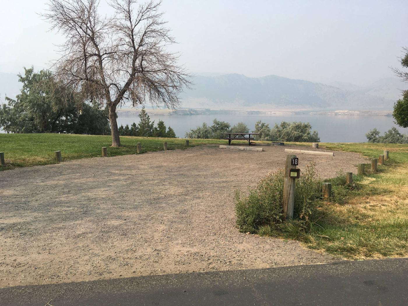 Site 18 BLM Holter Lake Campground. Lakeside campsite. Graveled campsite with picnic table and fire pit. Trees dispersed throughout campground.Site 18 BLM Holter Lake Campground