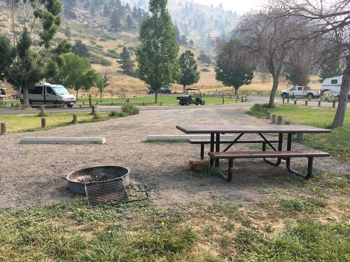 Site 18 BLM Holter Lake Campground. Lakeside campsite. Graveled pad with picnic table and fire pit on the lakeside of the campsite. Trees dispersed throughout campground. View of campsite.Site 18 BLM Holter Lake Campground.