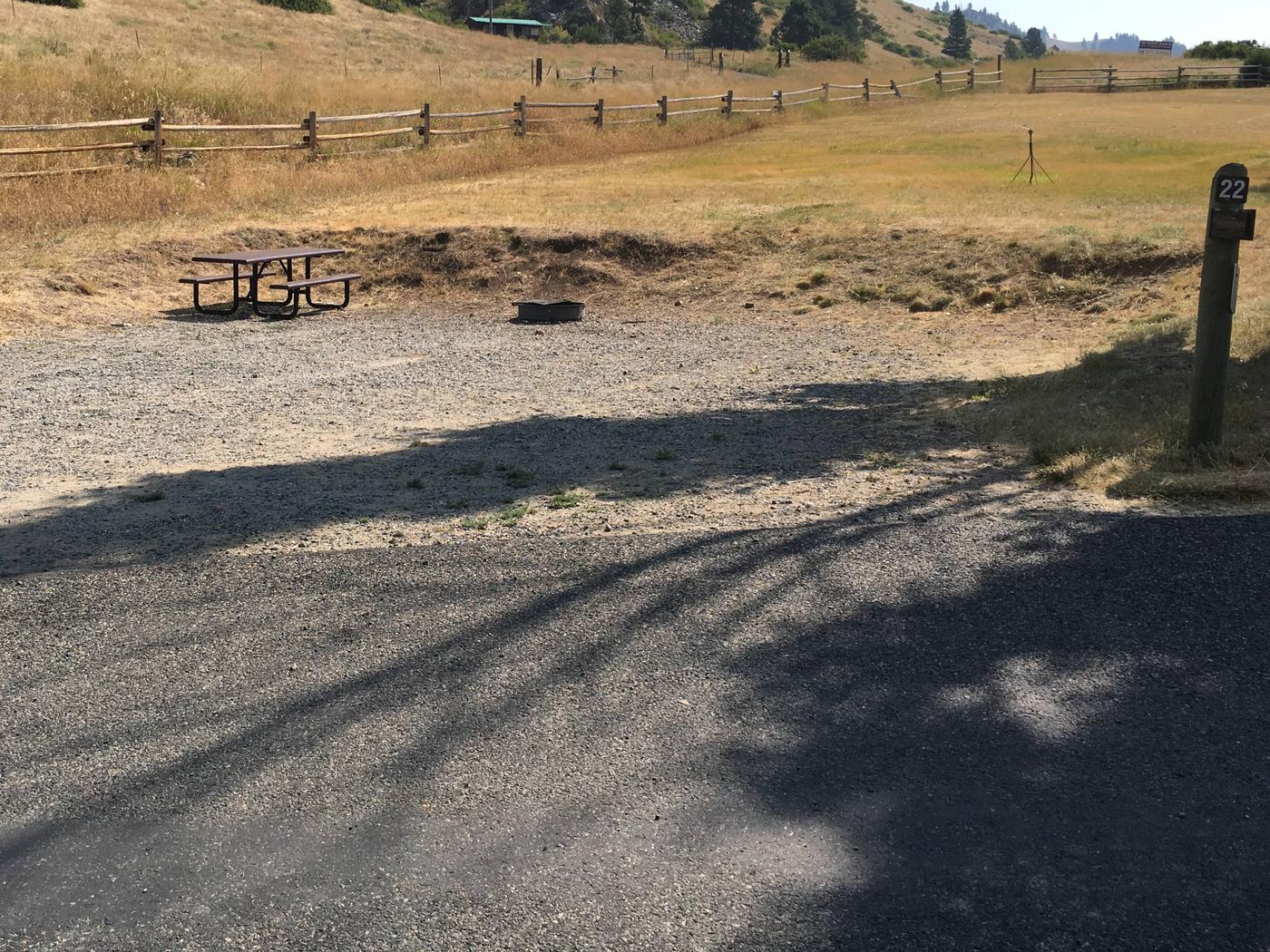 Site 22 BLM Holter Lake Campground. Paved access to campsite. Graveled campsite with picnic table and fire pit. Tree nearby campsite. Beartooth Road above the campsite.Site 22 BLM Holter Lake Campground.