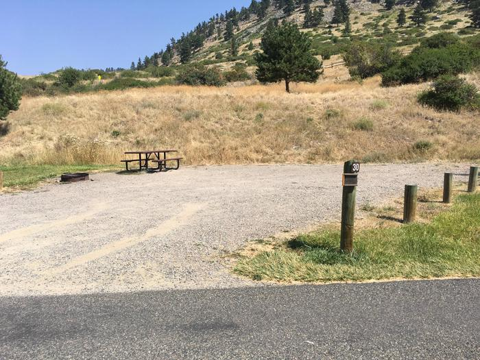 Site 30 BLM Holter Lake Campground. Paved access to campsite. Graveled campsite with picnic table and fire pit. Shrubs, trees and Beartooth Road above campground.Site 30 BLM Holter Lake Campground