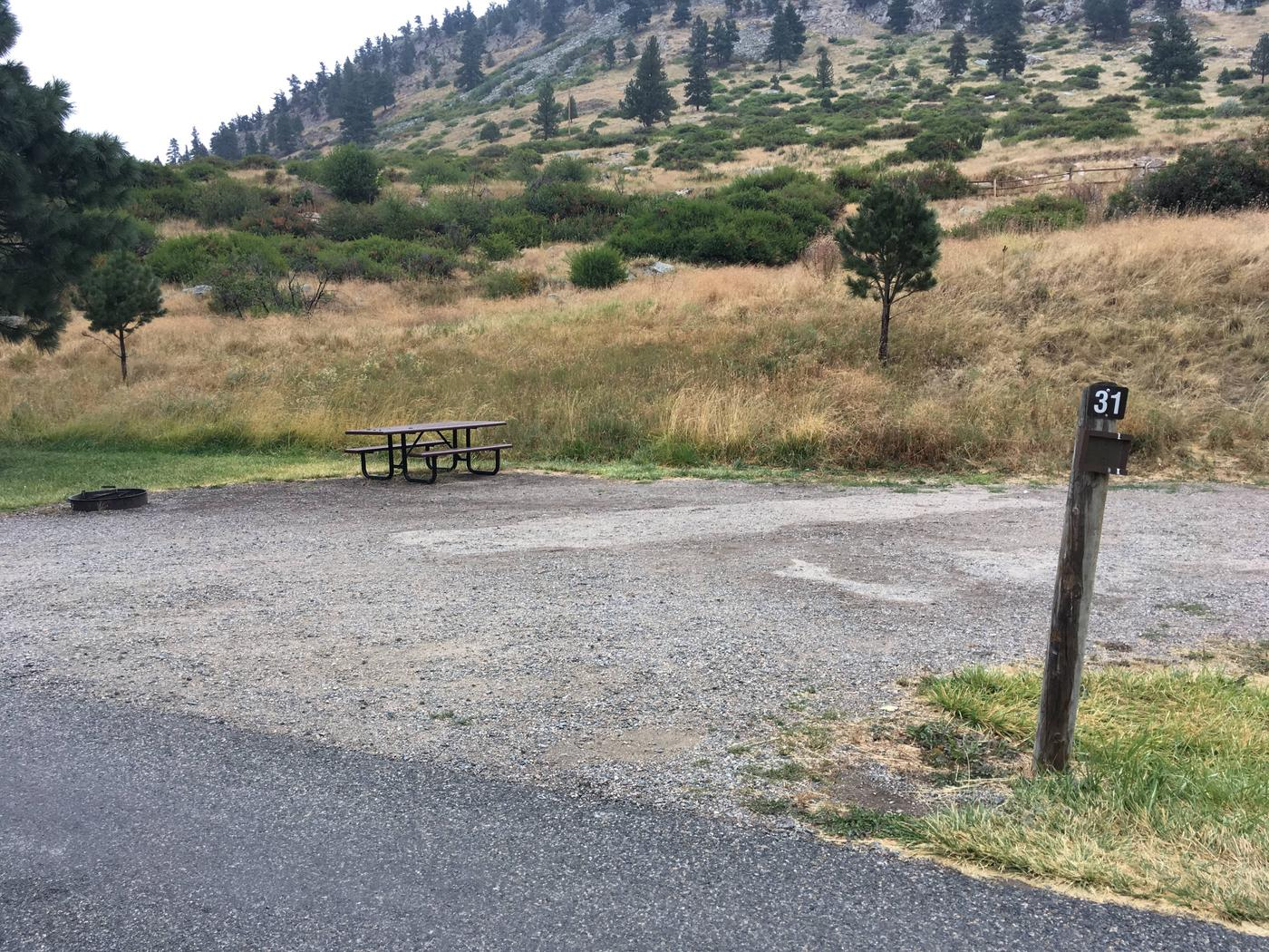Site 31 BLM Holter Lake Campground. Paved access to campsite. Graveled campsite with picnic table and fire pit. Beartooth Road above campground.Site 31 BLM Holter Lake Campground.