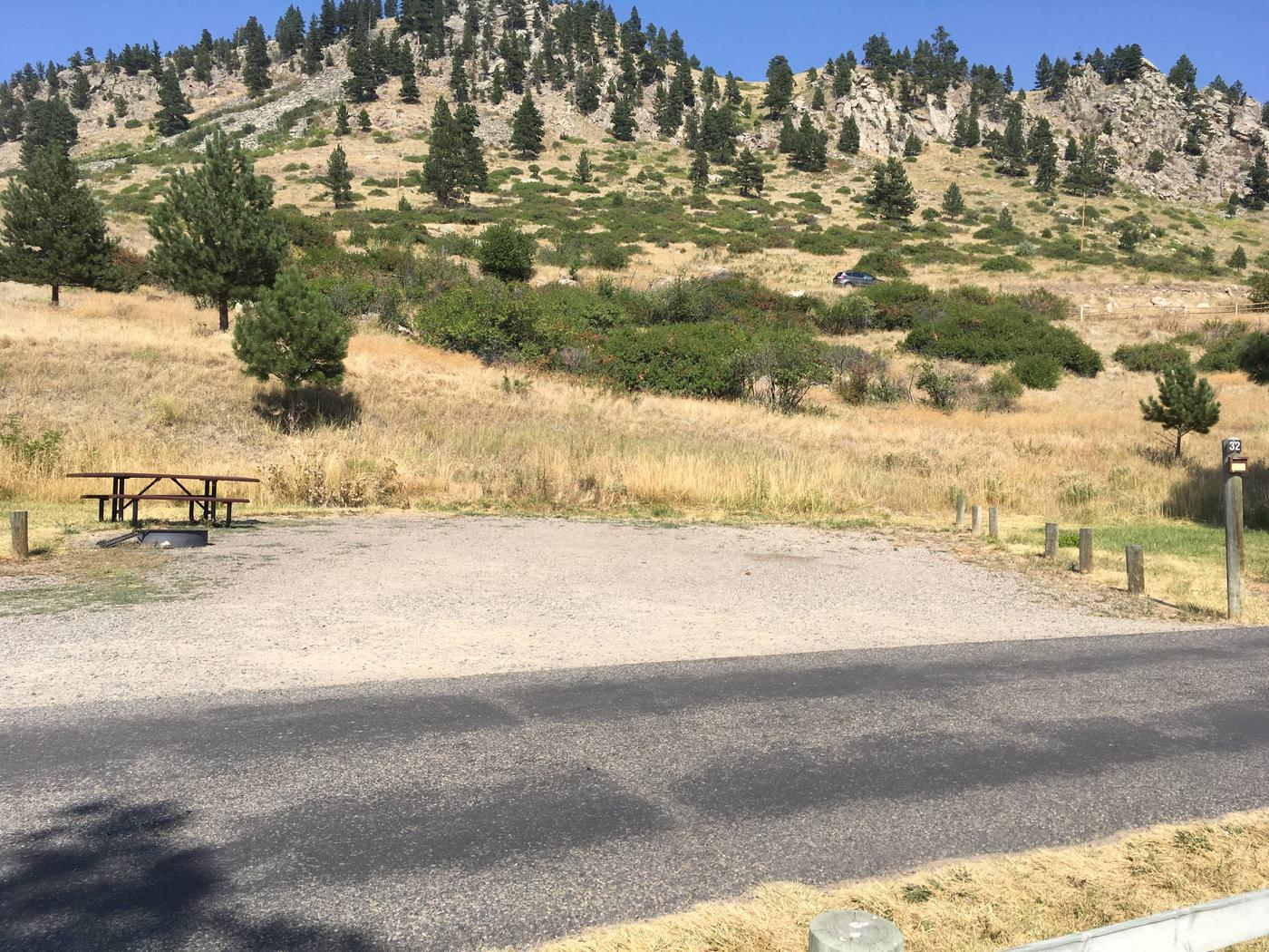 Site 32 BLM Holter Lake Campground. Paved access to campsite. Graveled campsite with picnic table and fire pit. Trees and shrubs above campsite. Campsite is below Beartooth Road.Site 32 BLM Holter Lake Campground.