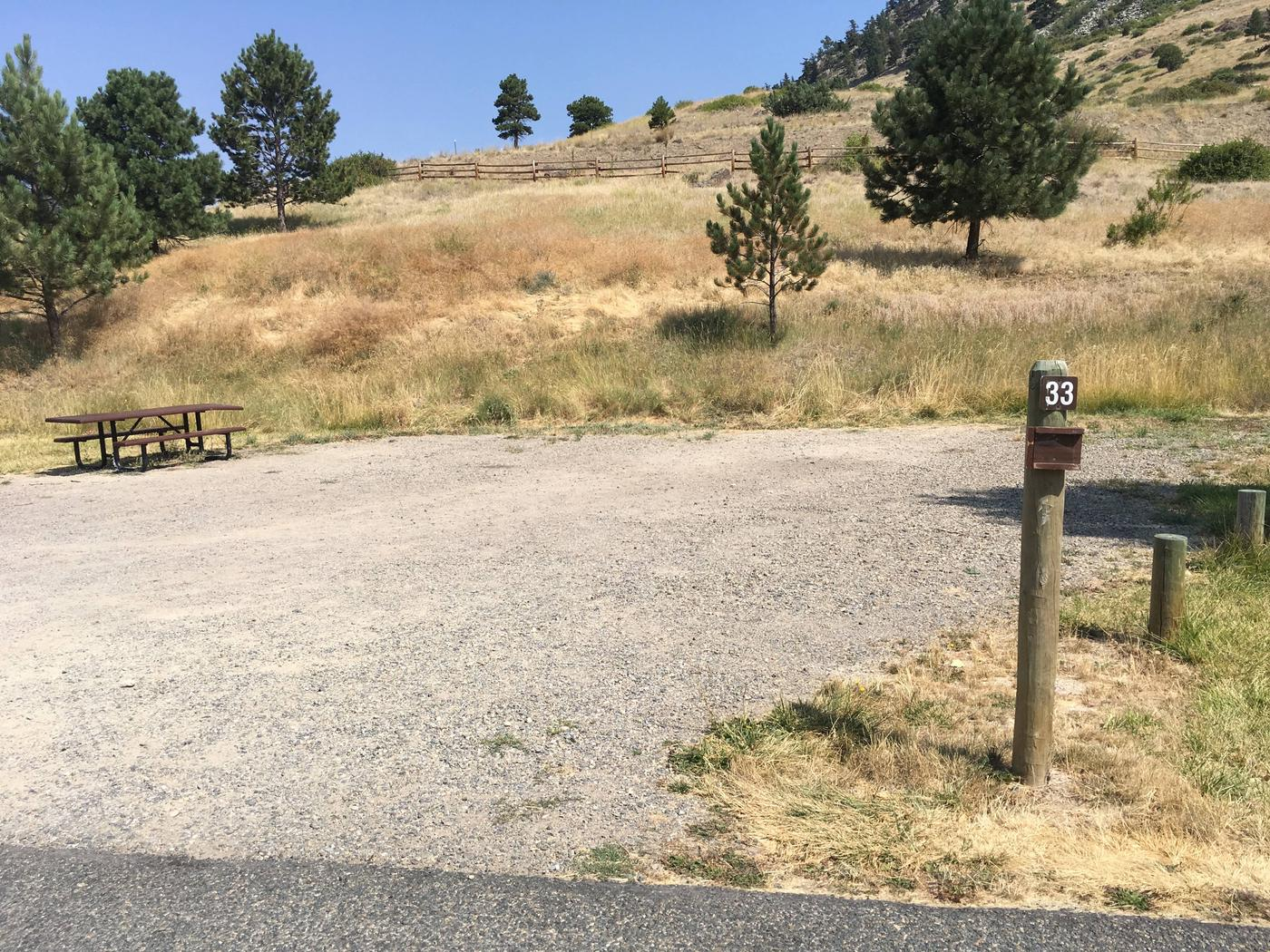 Site 33 BLM Holter Lake Campground. Paved access to campsite. Graveled campsite with picnic table and fire pit. Trees, shrubs and Beartooth Road above campsite.Site 33 BLM Holter Lake Campground