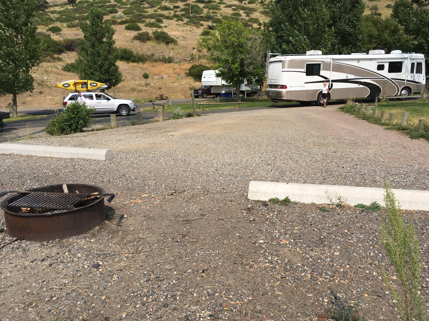 Site 8 BLM Holter Lake Campground. Interior view of campground from campsite. Graveled campsite with fire pit in the foreground.Site 8 BLM Holter Lake Campground.