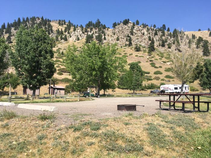 Site 12 BLM Holter Lake Campground. Interior view of campground from graveled campsite. Trees in the background. Fire pit and picnic table iin the foreground.Site 12 BLM Holter Lake Campground.