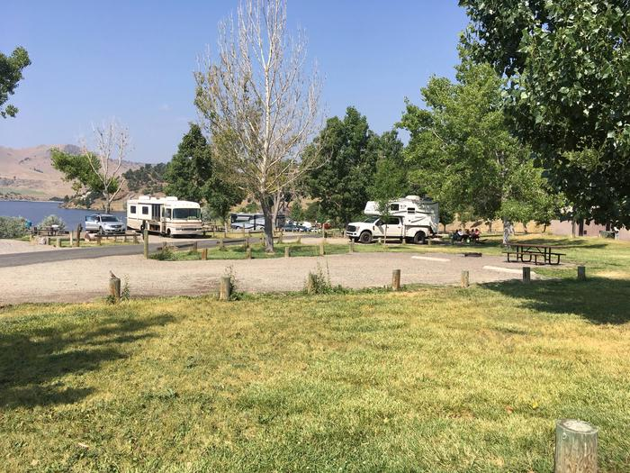 Side view of site 14 at BLM Holter Lake Campground. Grass and dispersed trees surround graveled campsite. Picnic table and fire pit are at the end of the campsite.Site 14 BLM Holter Lake Campground.