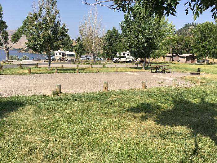 Side view of Site 16 at BLM Holter Lake Campground. Portion of Holter Lake visible. Graveled campsite surrounded by grass and wooden posts. Picnic table and fire pit at the end of the campsite.Site 16 BLM Holter Lake Campground