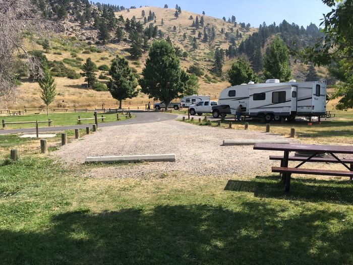 Lakeside campsite. View towards interior portion of campground with picnic table in the foreground and cement blocks to keep motorized equipment within the designated campsite. Potable water nearby. No hook-ups available. Must fill a container to use potable water hydrant.Site 19 BLM Holter Lake Campground.
