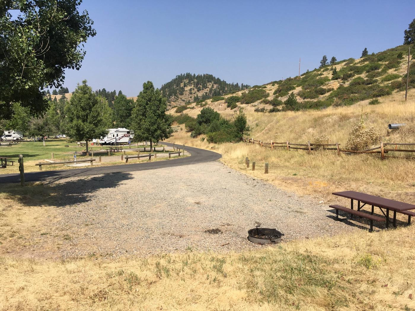 View of Holter Lake Campground from site 22. Paved access leads to graveled pad with picnic table and fire pit.Site 22 BLM Holter Lake Campground