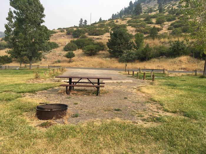 Site 25 BLM Holter Lake Campground looking towards hill and Beartooth Road. Fire pit and picnic table in the foreground of the graveled campsite with grass surrounding the campsite.Site 25 BLM Holter Lake Campground