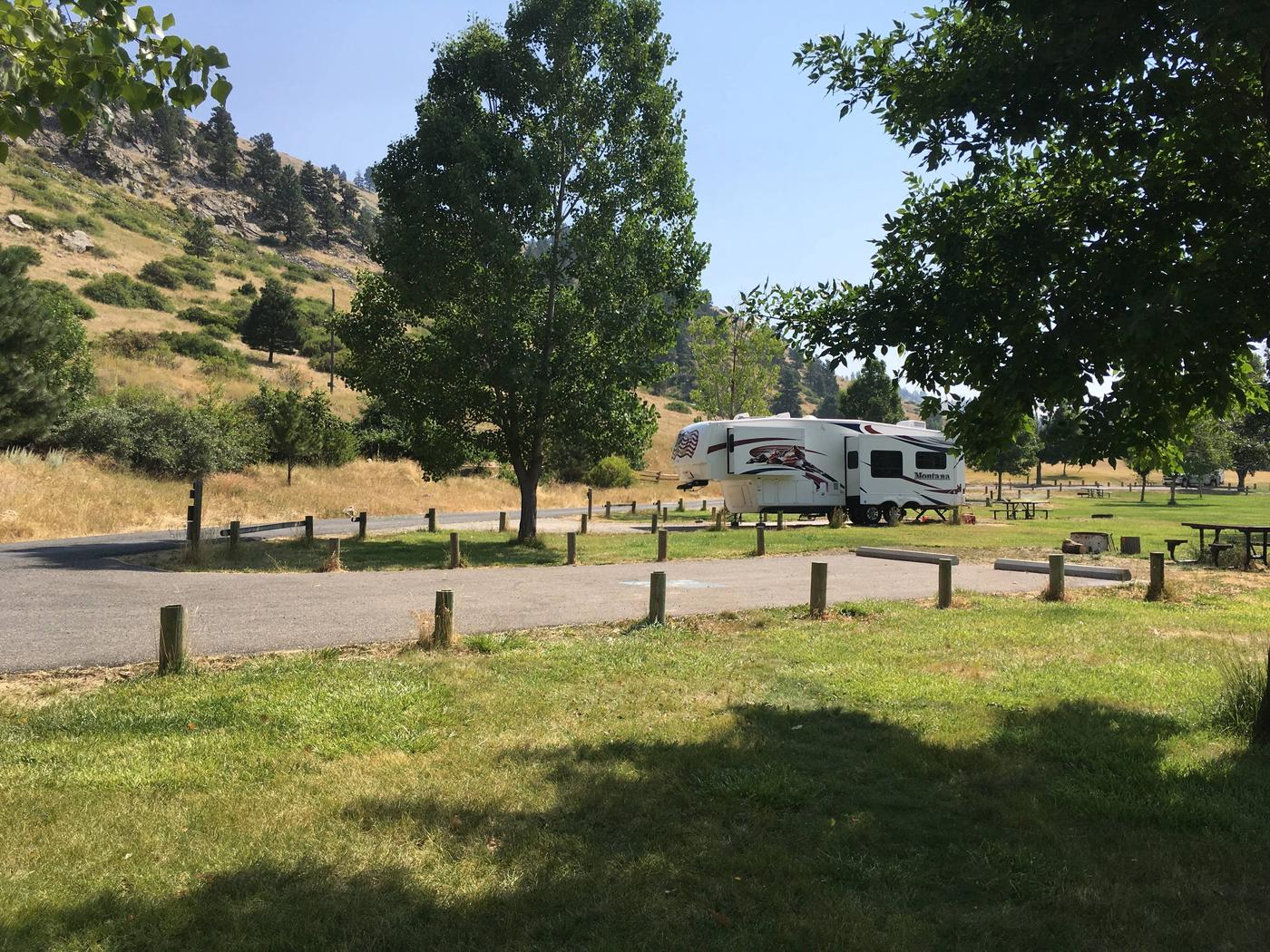 Side view of ADA site that is paved at Holter Lake Campground. Site 26 has paved access to the site. Picnic table and fire pit are at the far end of the campsite.Site 26 BLM Holter Lake Campground