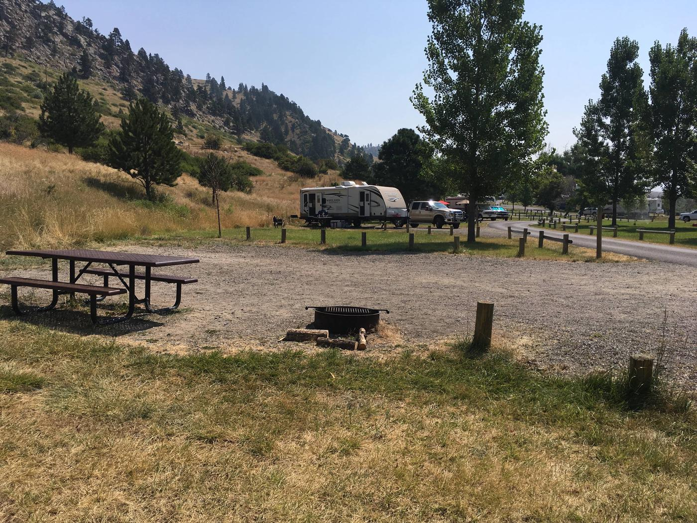 Side view of site 33 looking at the upper portion of Holter Lake Campground. Fire pit and picnic table in the foreground adjacent to graveled campsite.Site 33 BLM Holter Lake Campground