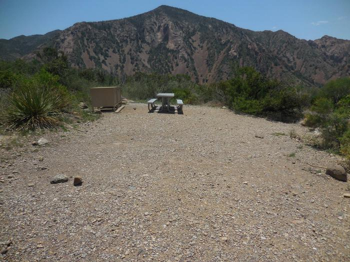 Flat, gravel area with picnic tables in the background, mountains in the distanceFlat, gravel area with picnic tables