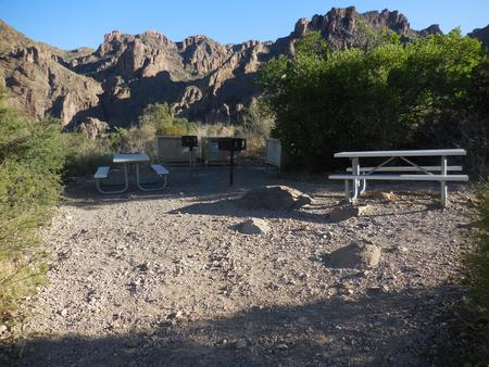 Picnic tables at campsite with mountains in the backgroundPicnic tables