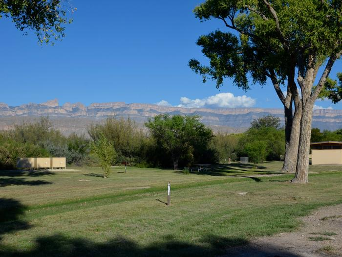 Open area among the shade of tall Cottonwood trees, adjacent to the bathrooms, mountains in the backgroundOpen area among the shade of tall Cottonwood trees, adjacent to the bathrooms