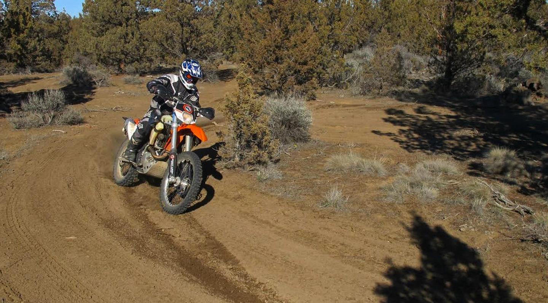 Motorcycling at Cline ButtesA dirt biker weaves through a juniper woodland near Cline Buttes.