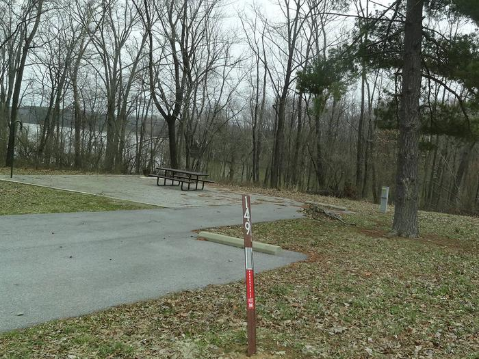 picnic table and fire pit to the left of camp pad, electric, water, and extra parking to the right of pad.