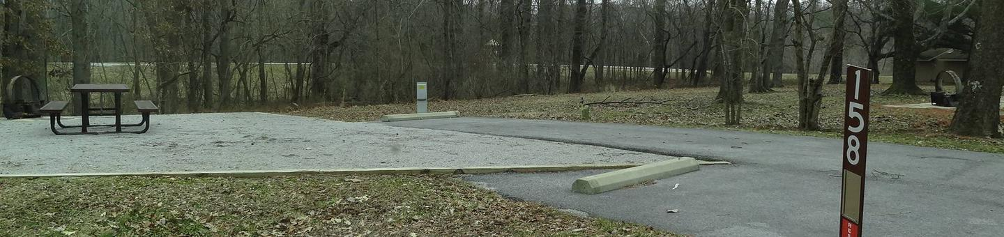 picnic table, fire pit, and extra parking to the left of camp pad, electric and water to the right of pad.
