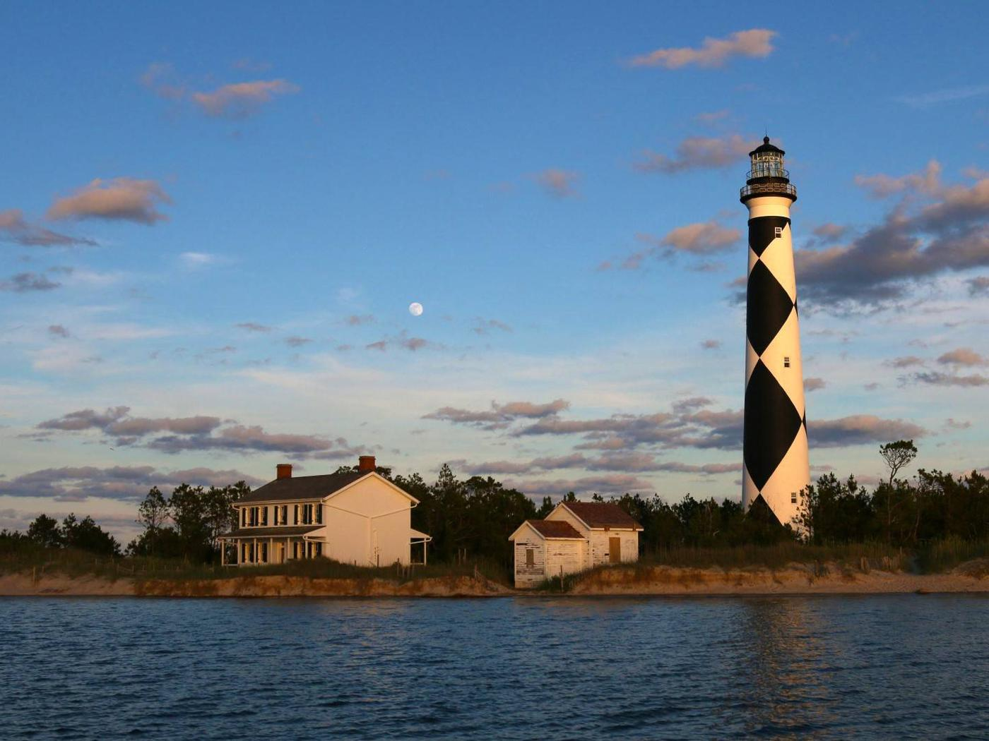 Cape Lookout Lighthouse area as the moon rises in the background at dusk.Cape Lookout's Lighthouse, Keepers Quarters Museum, and the Summer Kitchen is the setting of this magical evening tour.