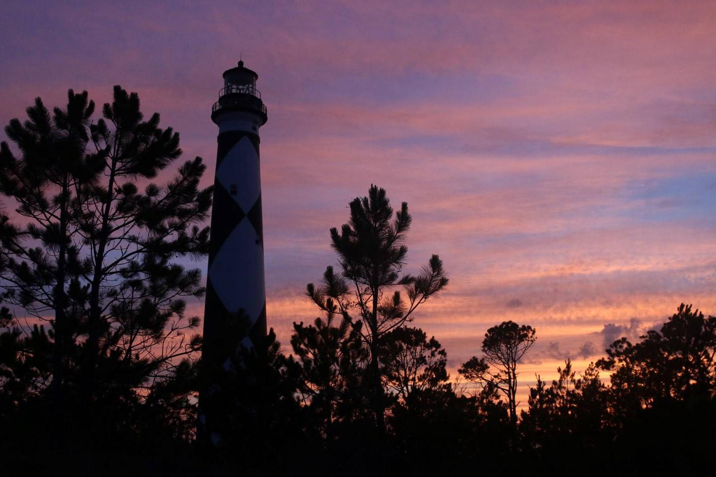 Silhouette of the Cape Lookout Lighthouse in the pink sky at dusk.  Dusk creates wondrous shadows and silhouettes across the South Core landscape on the Evening at the Cape tour.