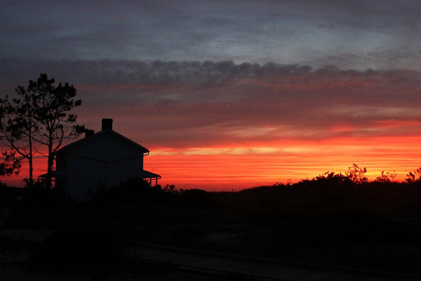 Silhouette of the Keepers Quarters with a red sky in the background.The view the Keepers had at dusk.