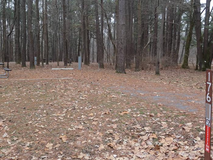 picnic table and fire pit to the left of camp pad, electric, water, and sewer to the right of pad.