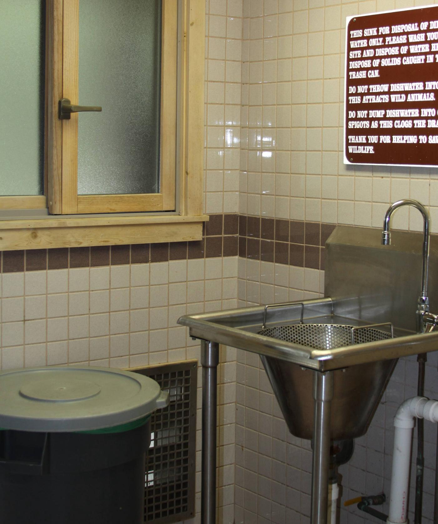 Dirty water disposal sink inside restroom buildingSink where campers pour dirty water from a container after washing dishes at campsite. (This is NOT a dishwashing station).