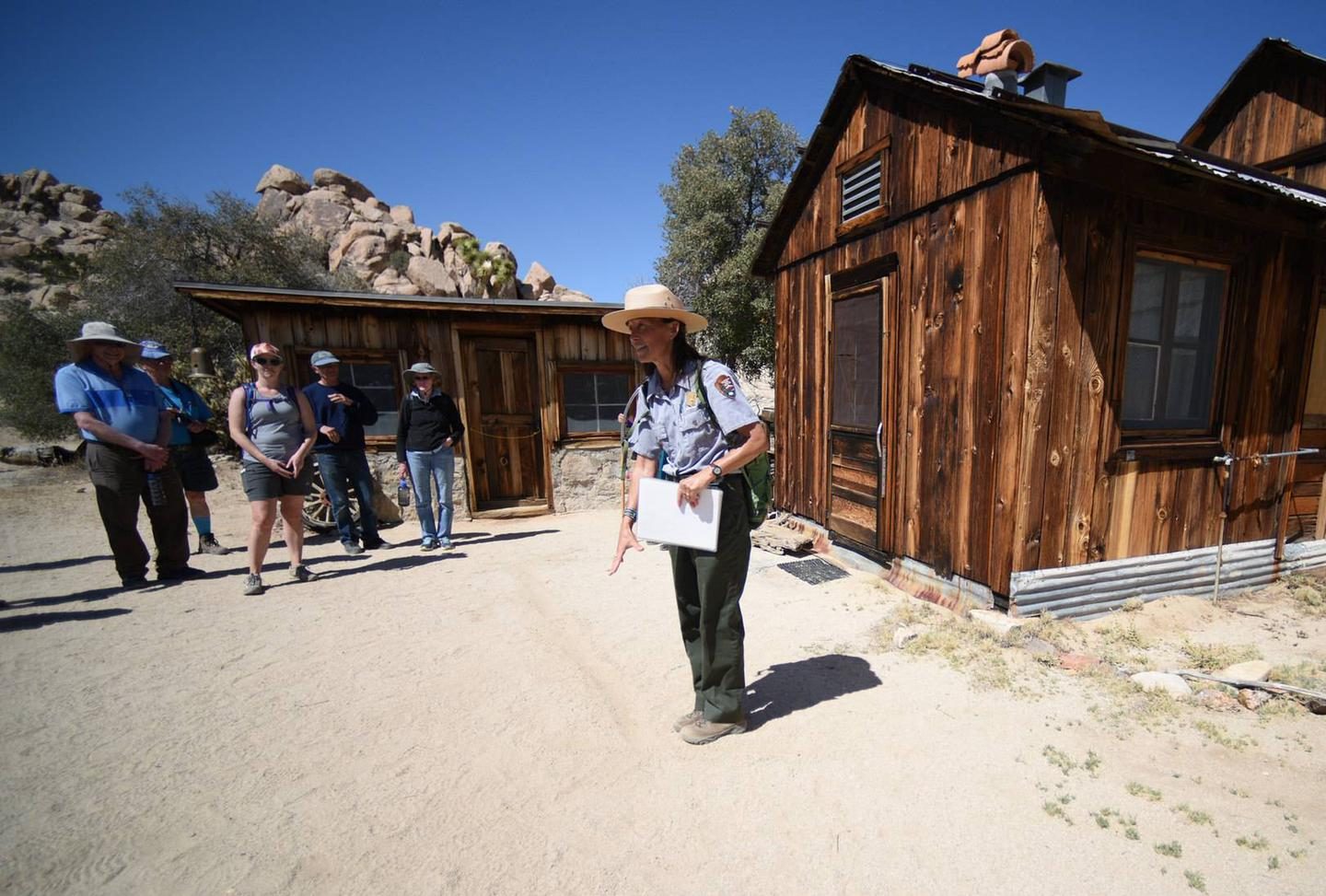 A woman wearing a NPS uniform is addressing a group of people in front of a historic ranch.Tours at Keys Ranch give visitors a unique experience to learn about the Keys family and their survival in a harsh desert environment.