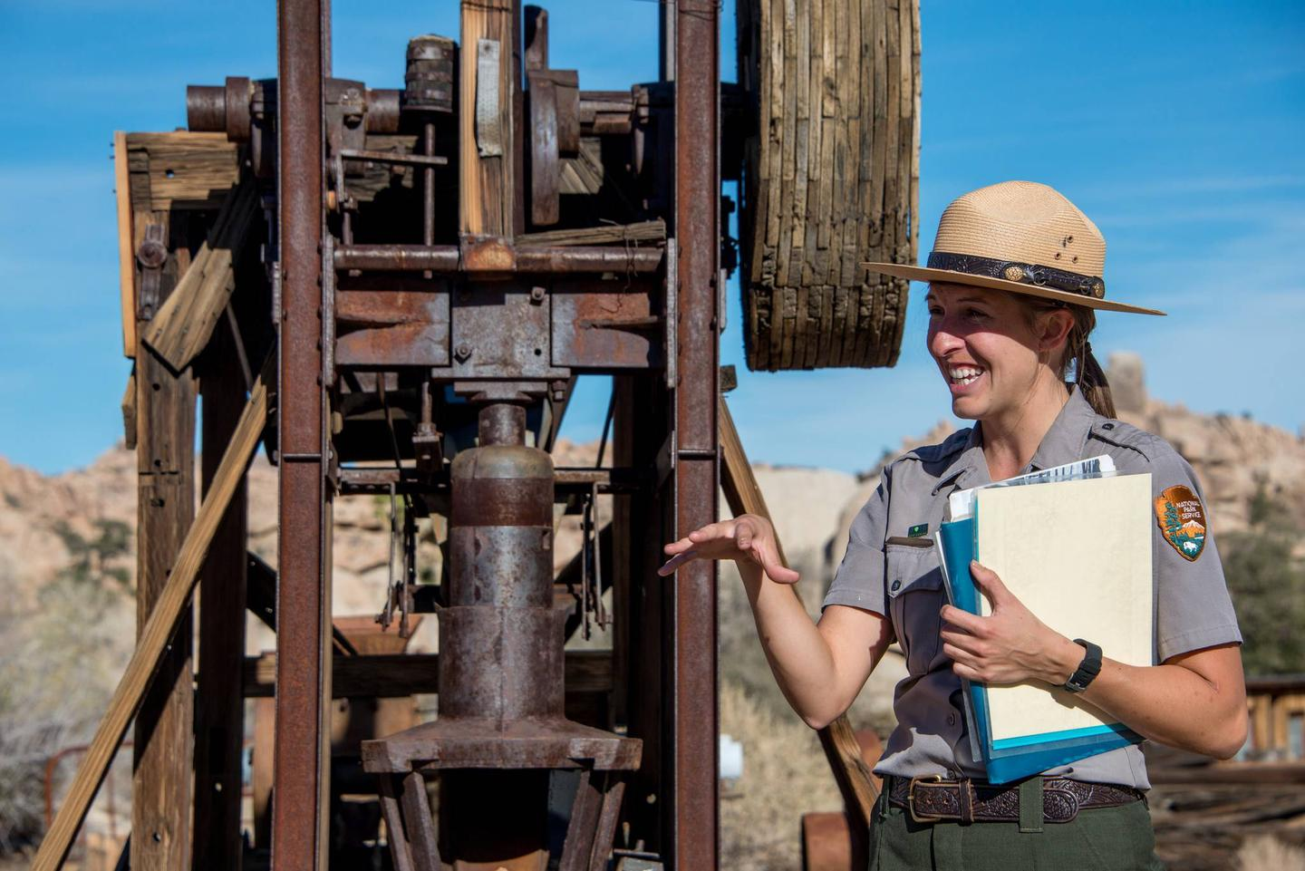 A woman wearing a NPS uniform is standing in front of an old gold mill.Gold mining was a way of life for many settlers in the region and old gold mills can still be found.