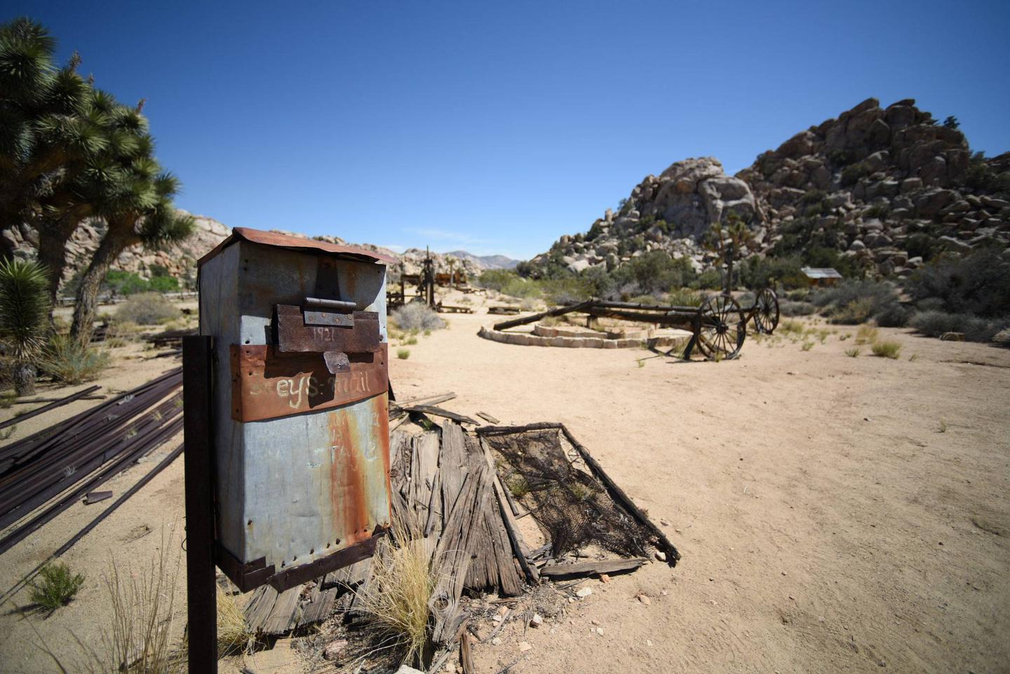 """A rusted tin box stands on a post with the words """"Keys mail"""" scratched into the side. In the background there is various rusted ranch equipment.Mail call! How long do you suppose it would take for a letter to arrive at Keys Ranch?"""