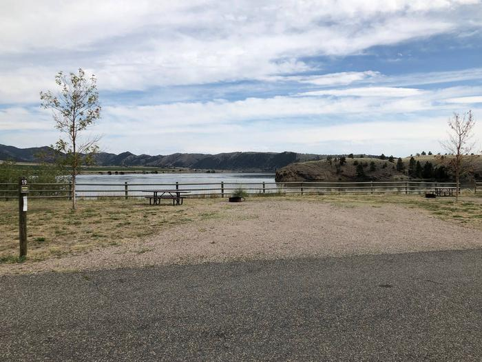 Site 19 BLM White Sandy Campground.  Lakeside campsite on Hauser Lake. Gravel camping pad with picnic table and fire pit. Paved access within campground. Wooden fence in the background to protect bank stabilization.Site 19 BLM White Sandy Campground.