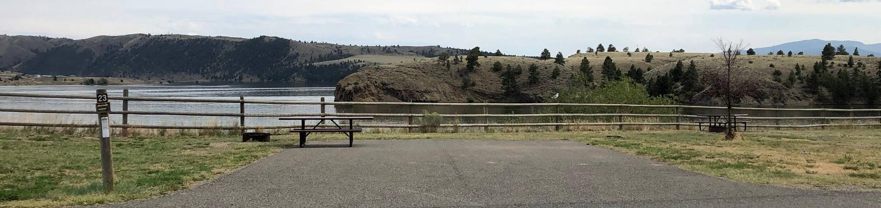 Site 23 at BLM White Sandy Campground. Paved access within campground. Paved camping pad with fire pit and picnic table. No shade at this location. Lakeside campsite on Hauser Lake. Wooden fence in the background to protect bank stabilization.Site 23 BLM White Sandy Campground.