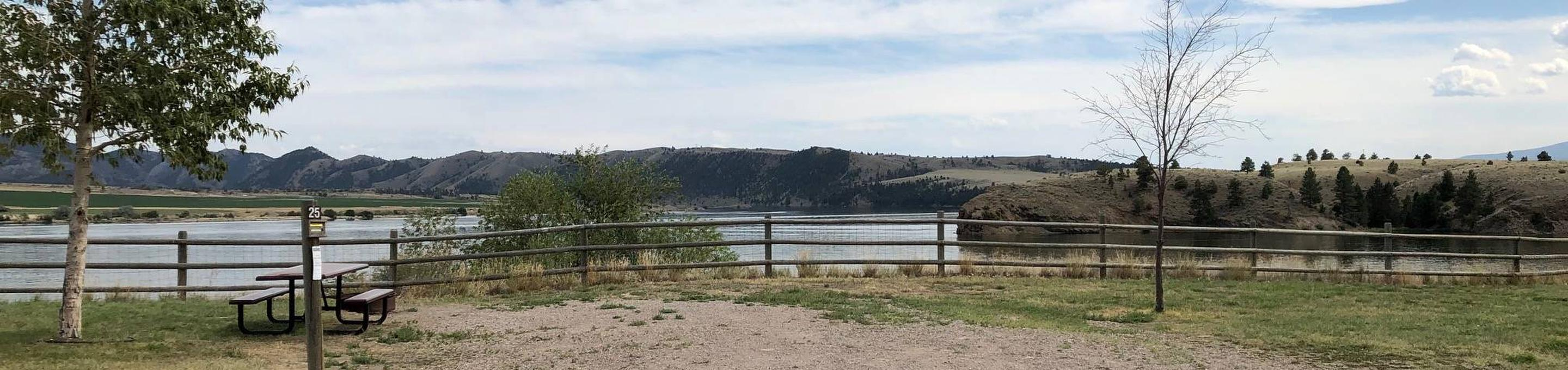 Site 25 at BLM White Sandy Campground. Paved access within campground. Gravel camping pad with fire pit and picnic table. Wooden fence in the background to protect bank stabilization. Lakeside campsite on Hauser Lake.Site 25 BLM White Sandy Campground.