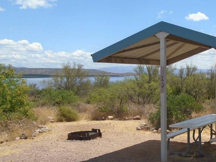 Campsite 13 at Cholla Campground with a picnic table, fire ring, shade structure, and parking.