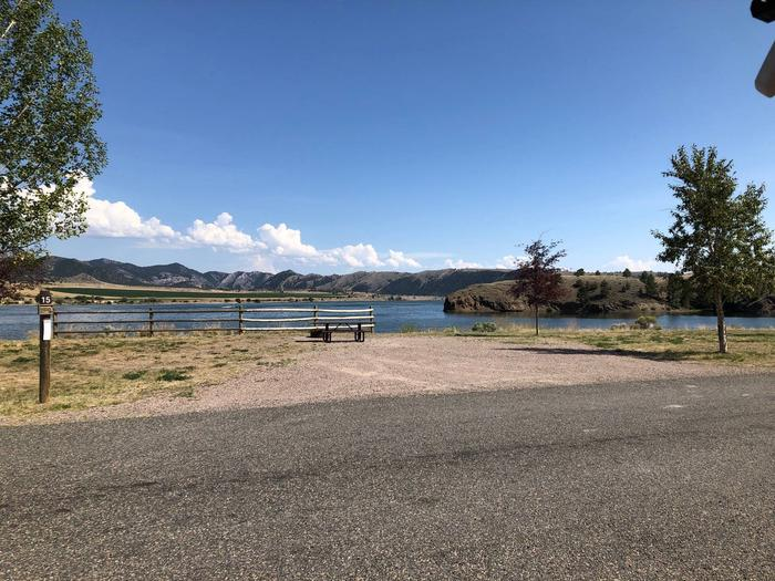 Site 15 BLM White Sandy Campground with gravel camping pad and paved access to site. Picnic table and fire pit at each campsite. Minimal shad from trees. Adjacent to Hauser Lake.Site 15 BLM Butte Field Office White Sandy Campground.