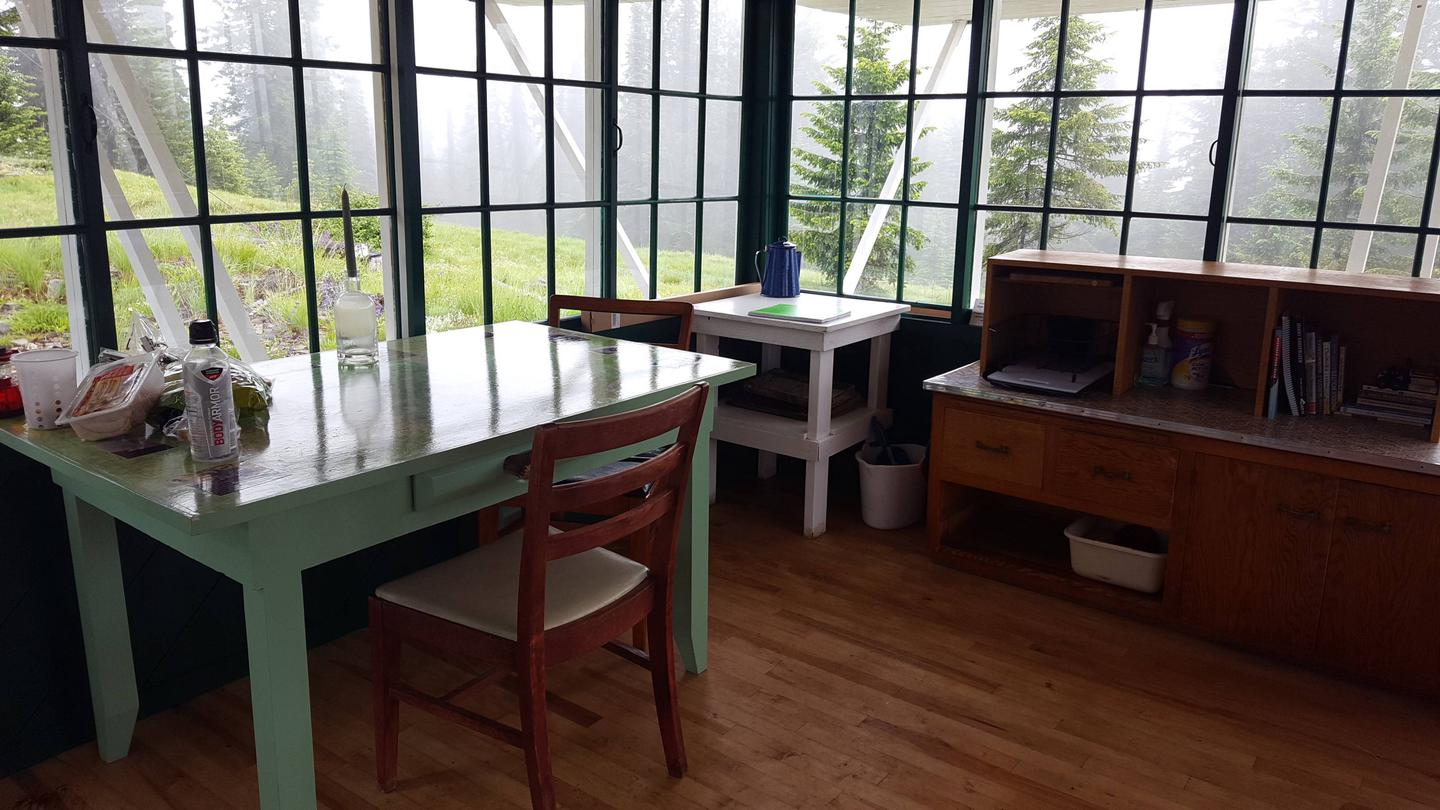 Interior 1A kitchen table and chairs and  cabinet with dishes and utensils is provided.