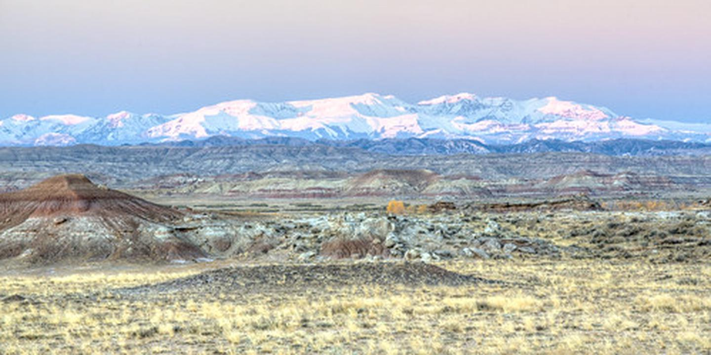 View of the badlands and snowy mountains