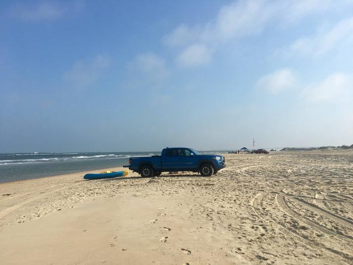 A blue truck on the beach with kayaks An ORV used to transport kayaks