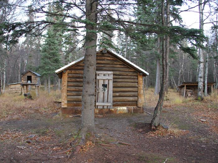 A cabin in the woods sits between a woodshed and a traditional food cache on stilts.The cabin entrance.