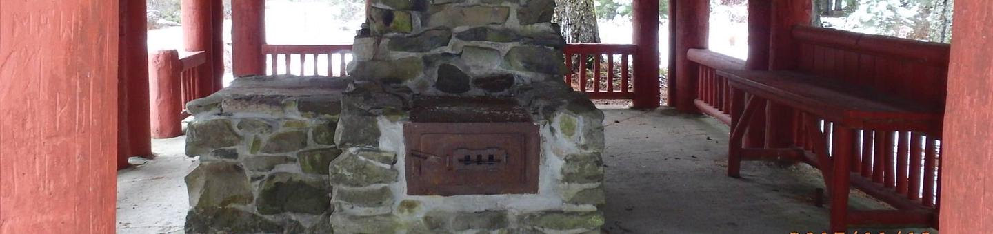 Stone fireplace and chimney next to counter under red-painted log shelter, brightly lit forest in background.CCC era picnic shelter