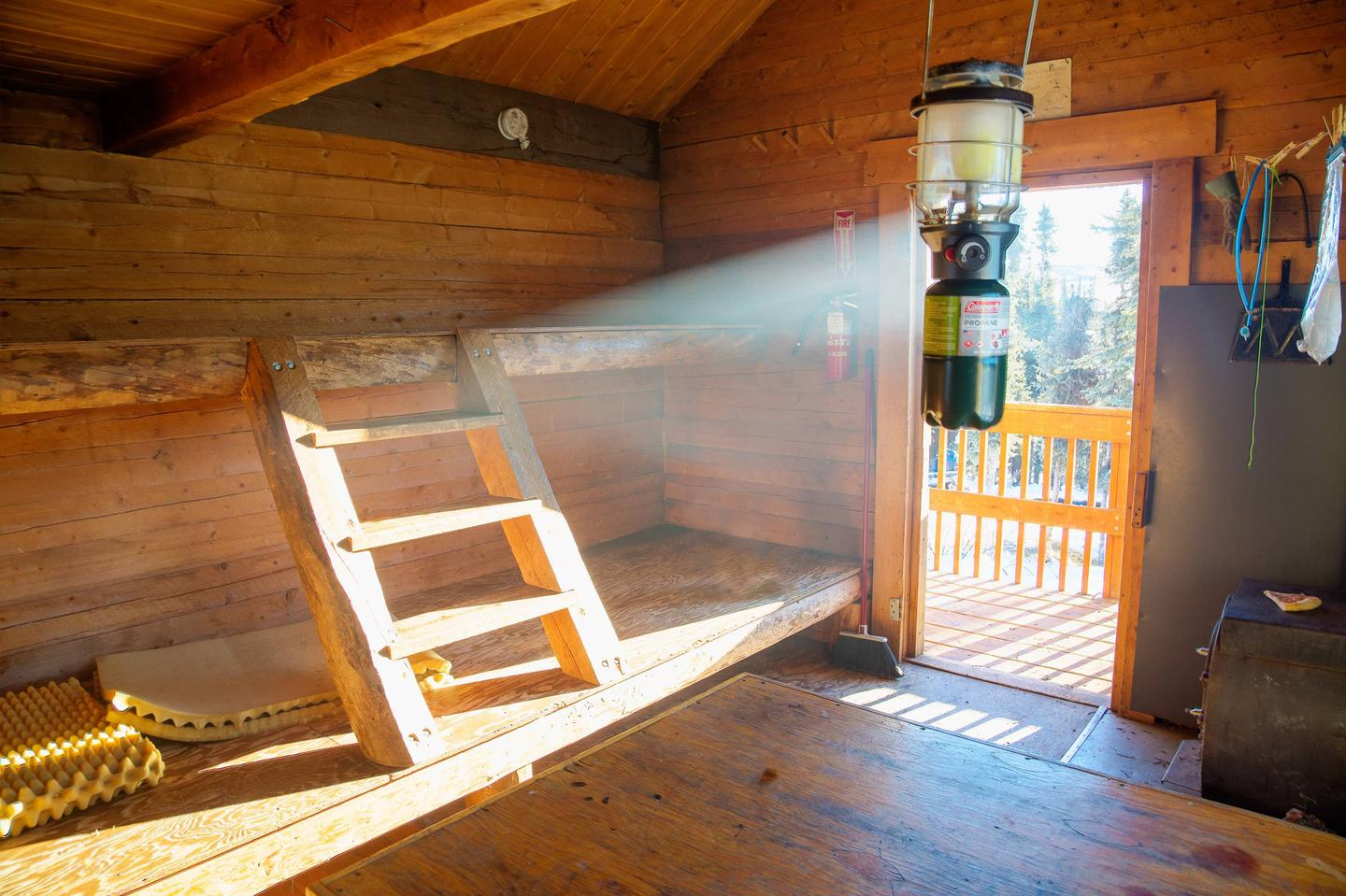 Sunlight streams through an open door into a log cabin.Borealis-LeFevre Cabin interior view of bunks and door.