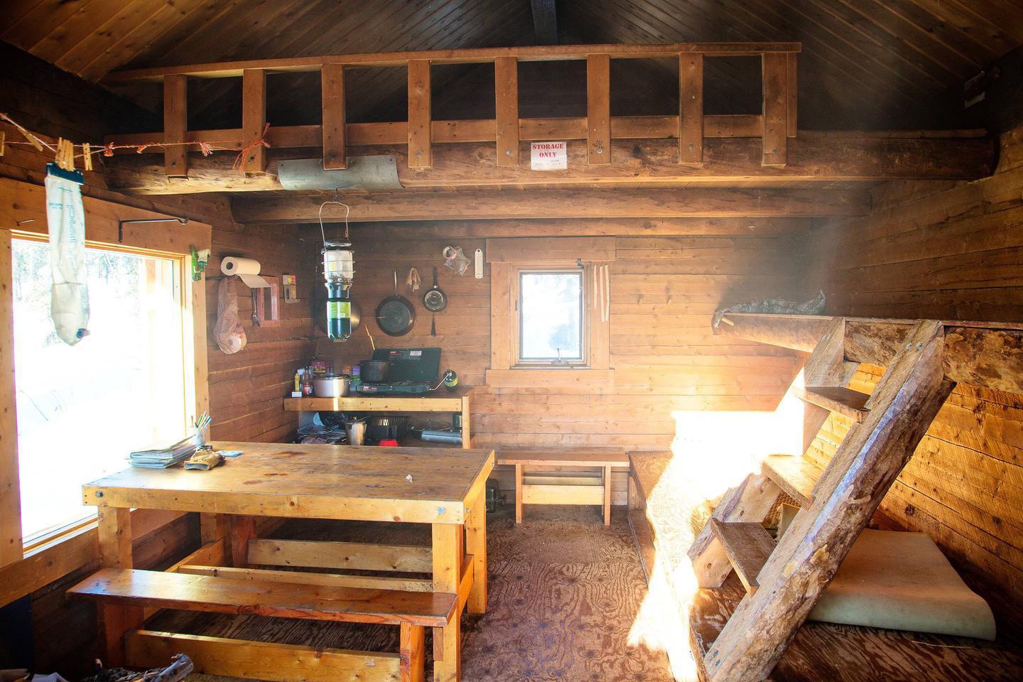 A log cabin interior includes bunks, a table with benches, and a loft.Bunks and cooking/eating area in Borealis-LeFevre Cabin.
