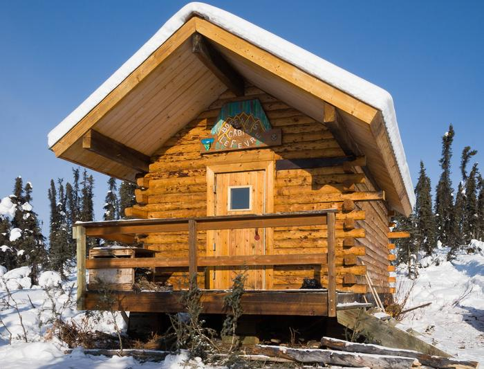A log cabin stands on a snow-covered hillside in a forest.Front of Borealis-Lefevre Cabin