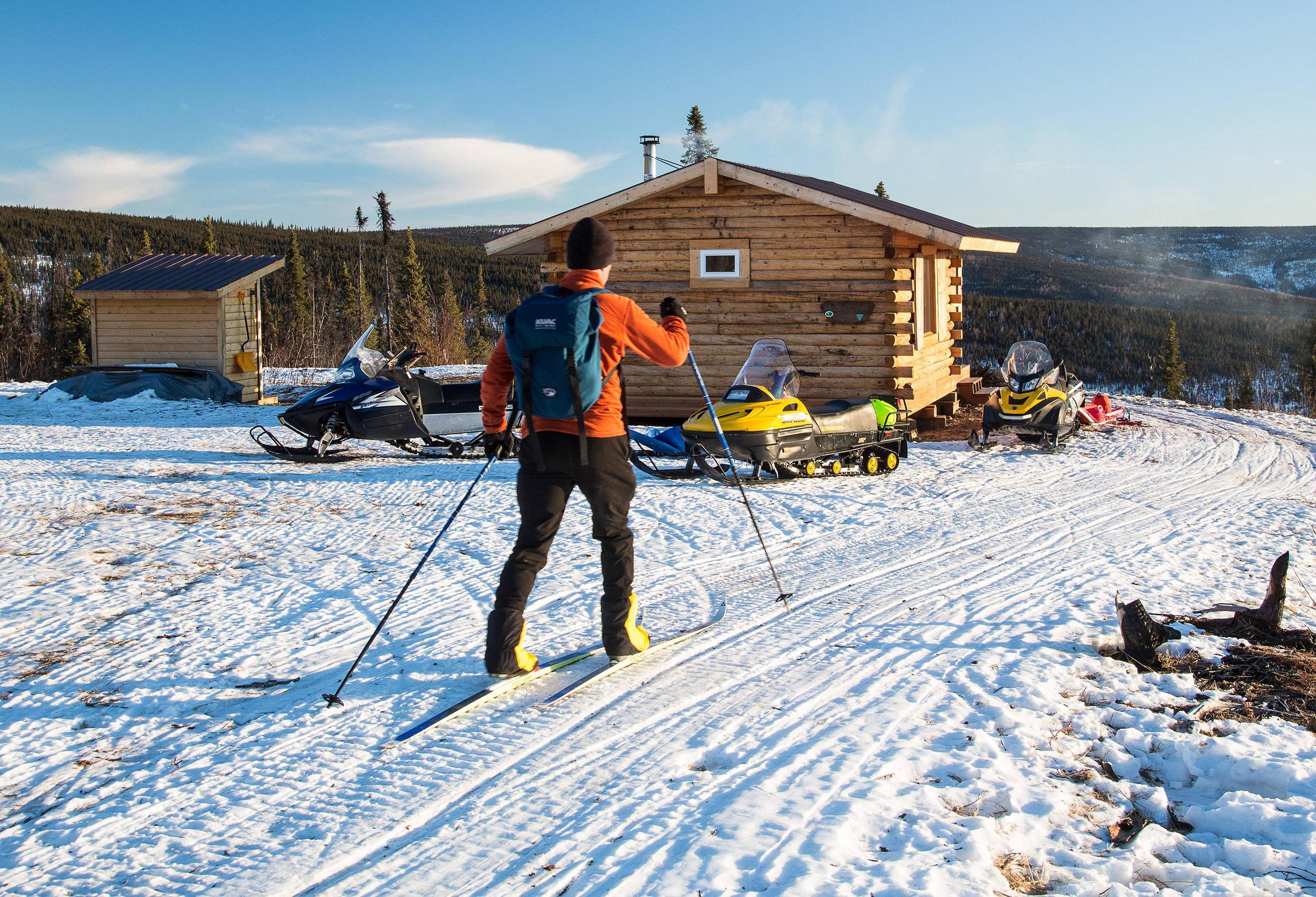 A man skies up to a log cabin surrounded by snowmobiles.Arriving at Moose Creek Cabin on skis.