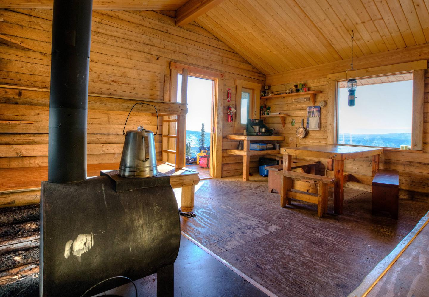 Cabin interior with woodstove, table, and benches.Interior view of Moose Creek Cabin